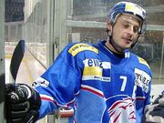 An ice hockey player stands looking to the right of the camera. He is wearing a blue and yellow heltmet and a blue uniform with a large white 7 on his chest.