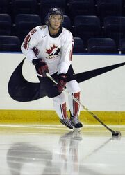 A hockey player in white Canada uniform skates across the ice, guiding the puck with his stick.