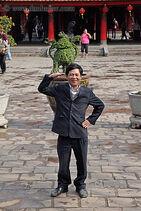 Asian-man-waving-n-smiling-big