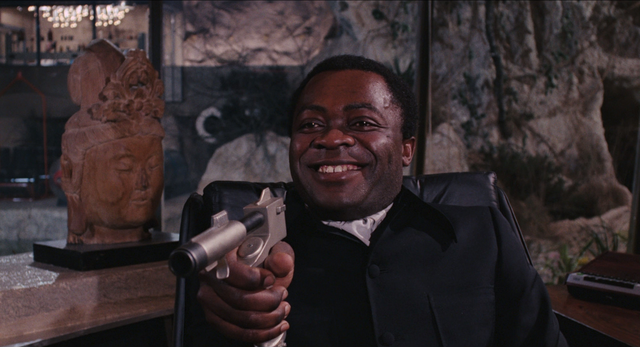 File:Live and Let Die - Kananga threatens Bond with his own weapon.png