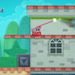 Kirby usando su látigo de hilo para descubrir un lugar secreto.