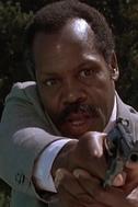 Roger pointing gun at pool man