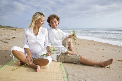 File:6683526-happy-young-pregnant-couple-relaxing-on-beach-sitting-together-on-sand.jpg