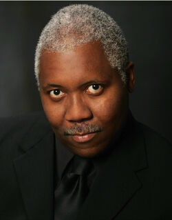 Head and shoulders of an older African American man with short, gray hair in all-black formal wear