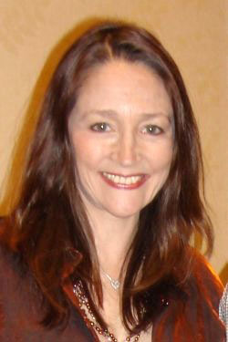 Head and shoulders of an older woman with long brown hair smiling