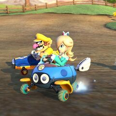 Rosalina, Wario, and Metal Mario race on the track.