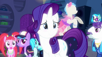 Rarity looks at her friends while blushing S6E9