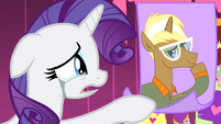 Rarity looks at a photo of Trenderhoof S4E13