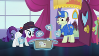 Rarity levitates crumpled papers out from the package S5E15