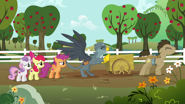 File:Gabby pushes Dr. Hooves' cart out of the mud S6E19.png