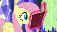 Fluttershy looking at Twilight's levitating book S5E23