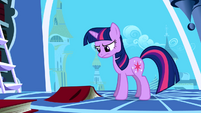 Twilight frowning at a book on the floor S1E01