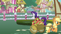Applejack trots away with her cart of apples S7E9