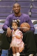 Kobe Bryant of the Lakers sits down with his daughter Natalia in between his legs