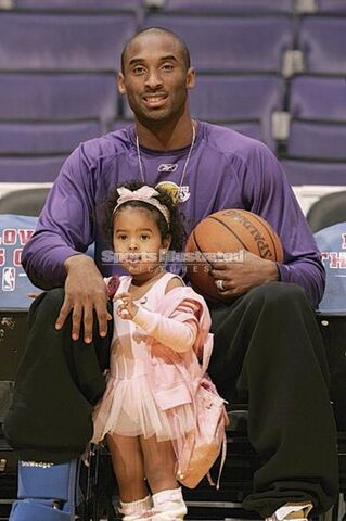 File:Kobe Bryant of the Lakers sits down with his daughter Natalia in between his legs.jpg