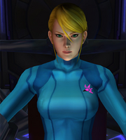 A computer-generated image of a woman wearing a tight-fitting blue suit. She has blond hair and green eyes, and appears to be sitting in a chair.