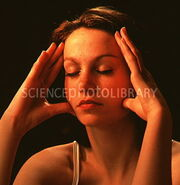 M7650097-Meditating young woman s face with hands on temple-SPL