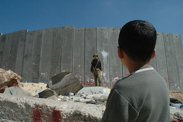 File:Boy and soldier in front of Israeli wall.jpg