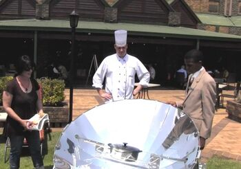 Thea Holm demonstrates solar cooking to chef, 2-21-13