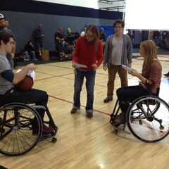 Cample and Daphne playing basketball in a wheelchair