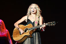 A female teen with blond hair and blue eyes, clothed by a sparkly dress, faces forward and plays a koa wood guitar.