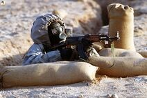 Syrian soldier aims an AK-47