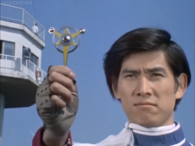 File:Kotaro holds the Ultra Badge for the last time.png