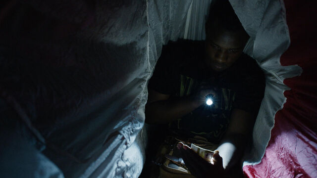 File:Little Thing 1x08 Mohamad in a tent looking at a photo.jpg