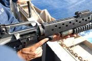 US Navy 080806-N-7730P-202 Aviation Electronic's Technician 3rd Class Awail Hassen loads a high explosive point detonated 40MM grenade round into an M203 grenade launcher