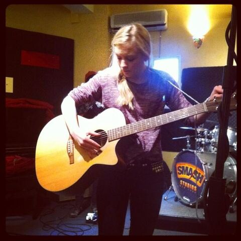 File:Emily checking her guitar before performing.JPG