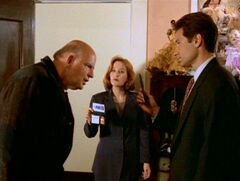 Clyde Bruckman looks at Fox Mulder's and Dana Scully's badges