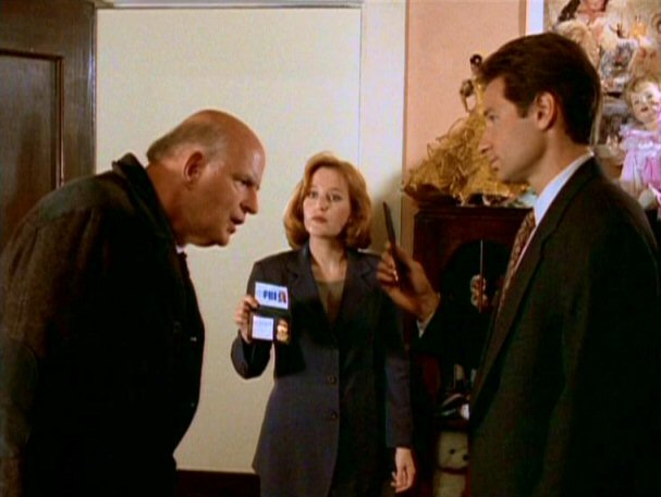 File:Clyde Bruckman looks at Fox Mulder's and Dana Scully's badges.jpg