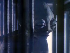 Grey alien smokes cigarette