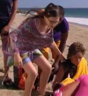 Quinn grabs onto Logan's shoulder for support.